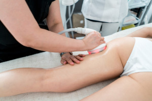 Woman getting an anti-cellulite laser treatment at the spa on her legs - beauty concepts